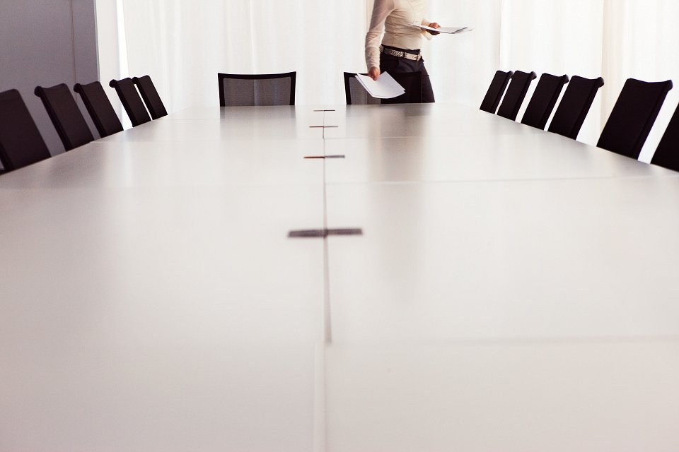 Igor Emmerich, work. Woman lays documents on boardroom meeting table