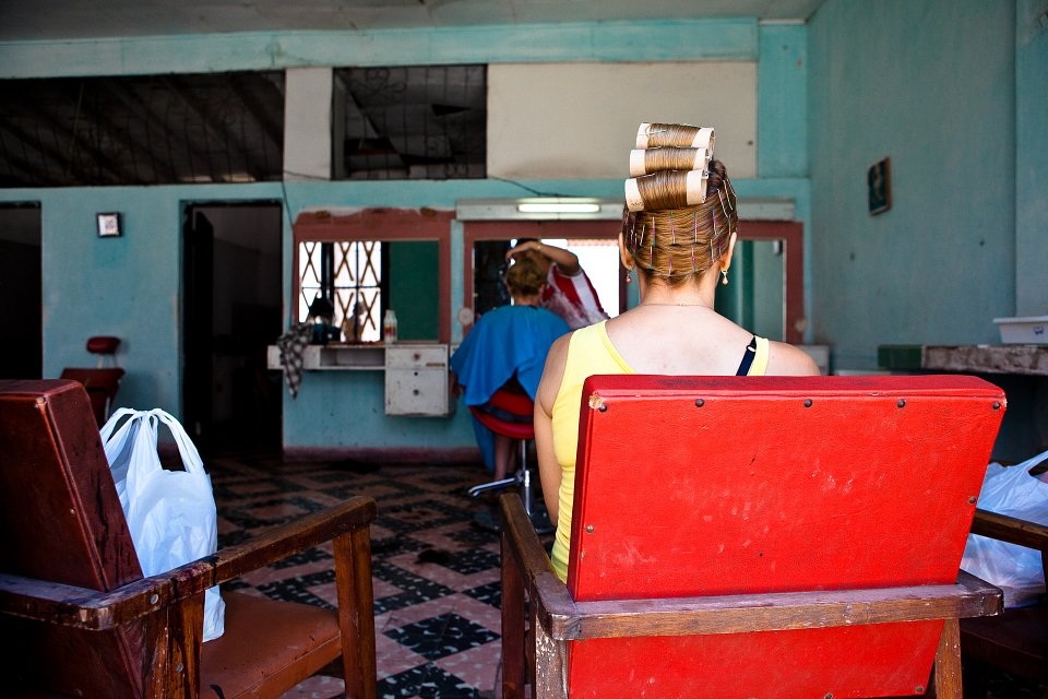 Igor Emmerich. Cuba. Woman sits wearing curlers in hairdressers