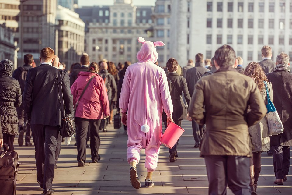 Igor Emmerich, Tangible. Individuality. Charity worker dressed in pink bunny costume walks with commuters across bridge in city