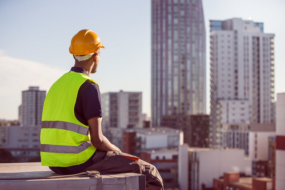 Igor Emmerich. Builder in high visibility and hard hat sits on roof overlooking the city