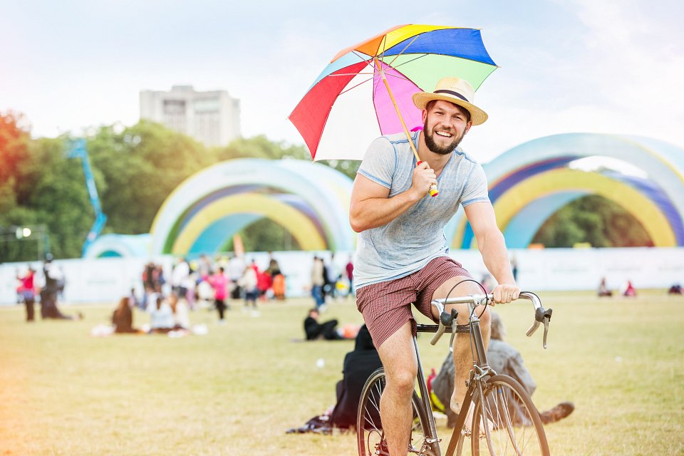 Igor Emmerich. Getty. Summer. young man on bicycle with umbrella in park at festival. Summer