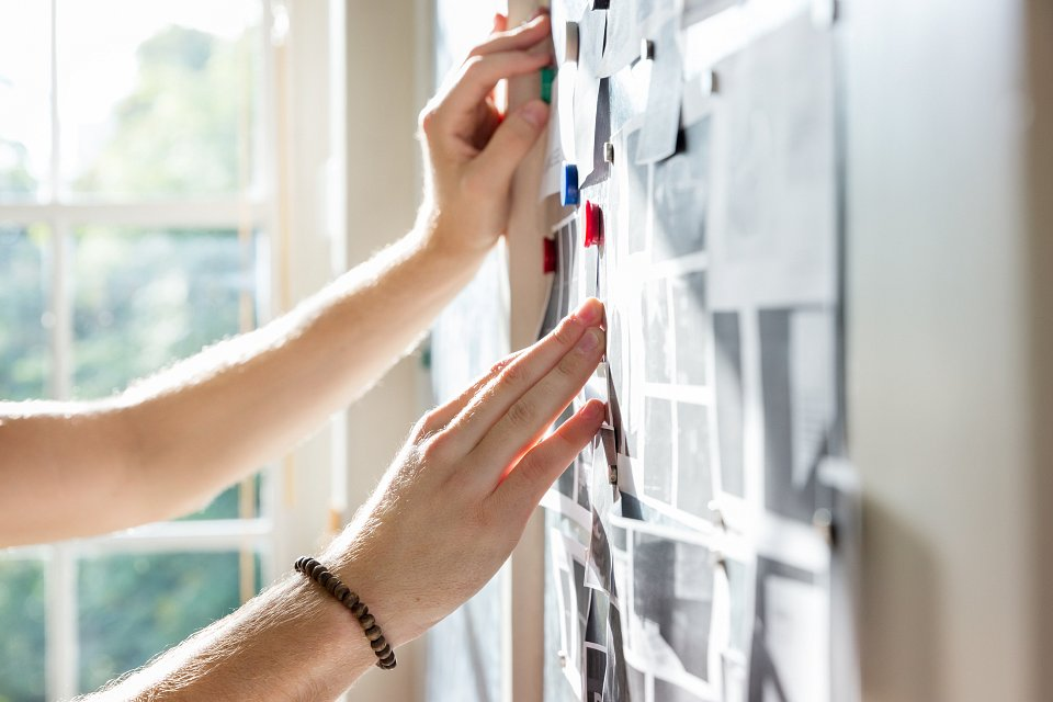 Igor Emmerich, Creative Office. Hands on a pin board by a window in office