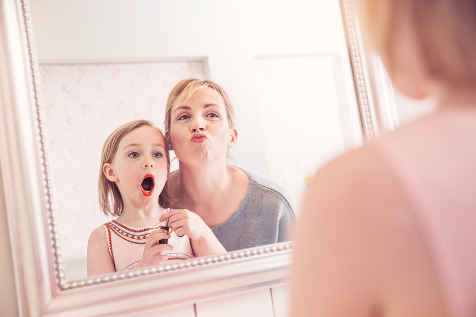 Igor Emmerich, Corbis. Mum and daughter play with lipstick in front of bathroom mirror