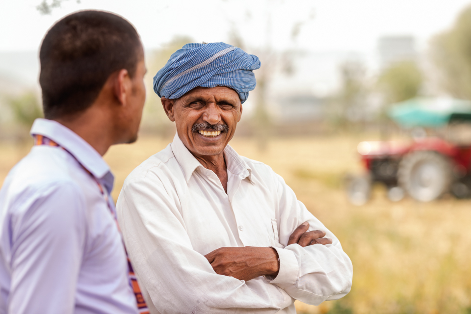 Igor Emmerich, portrait of a farmer on a field in front of his tractor talking to a bank manager in Jaipur