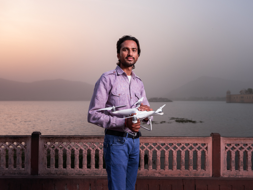 Igor Emmerich, drone operator standing infant of a lake at sunrise in Jaipur.