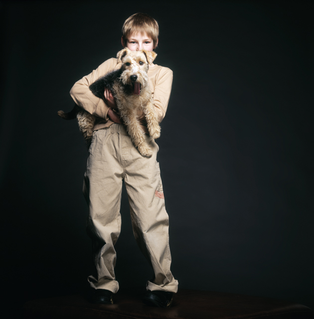 Igor Emmerich portrait photographer, portrait of a boy in the studio against a dark background holding a terrier dog, london, uk