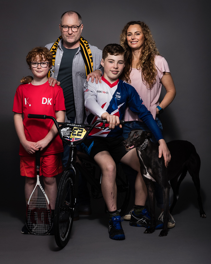Igor Emmerich, advertising photographer, photographer, portrait photographer, uk photographer, London photographer, kent photographer, england, Portrait of a family with kids and dog and hamster shot in a studio against a dark background