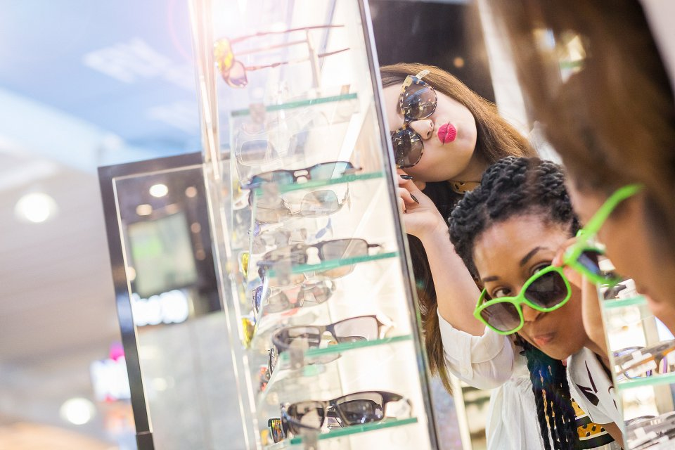 Igor Emmerich, Ico Design, London Luton Airport, young women trying on sunglasses in airport duty free, shopping