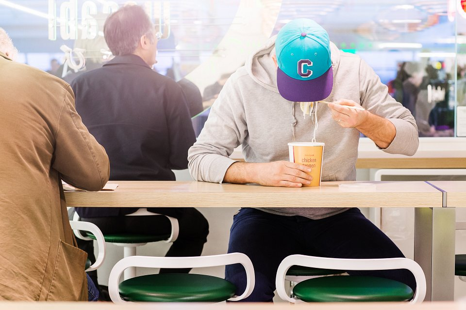 Igor Emmerich, Ico Design, London Luton Airport, young man in baseball cap eating noodles at airport restaurant