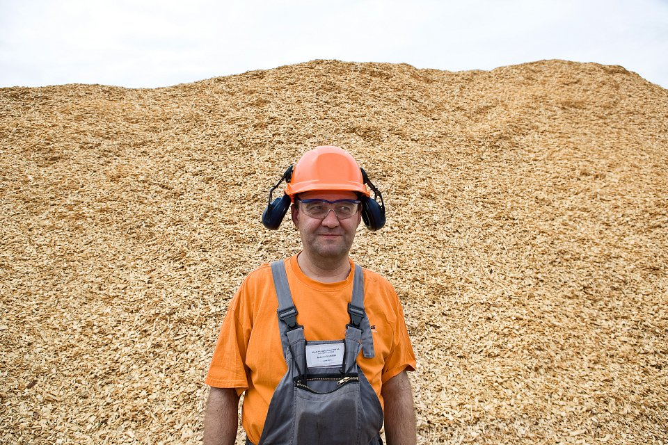 Igor Emmerich, Mondi Worker in hard hat and ear defenders in from t of wood chip